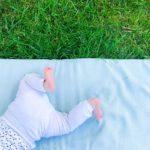 pieds de bébé sur tapis d'éveil dans l'herbe