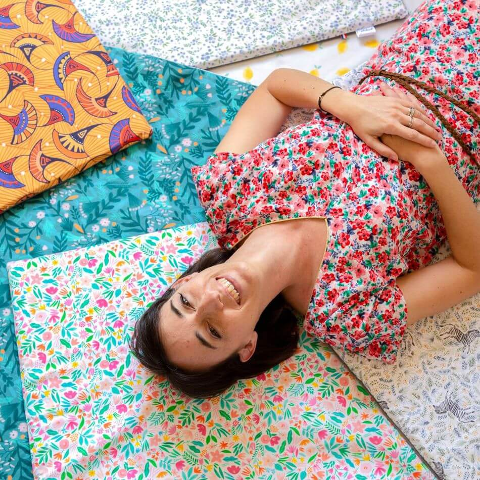 Femme souriante sur plusieurs tapis d'éveils colorés